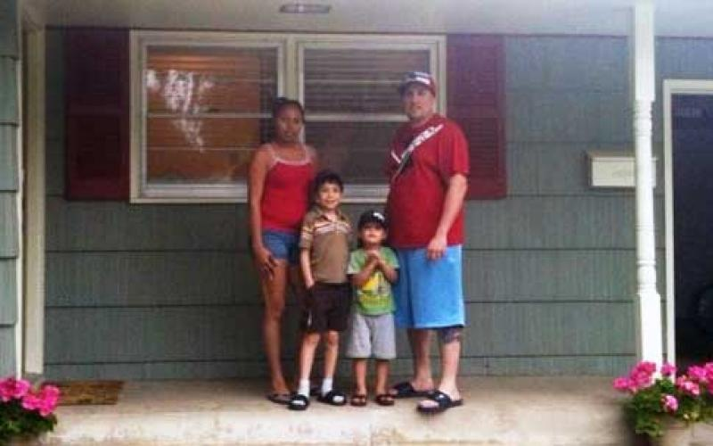 A family of four in front of their home