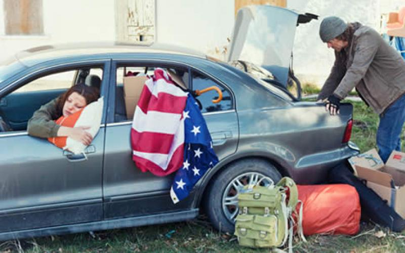 A woman in the front seat of a car while a man is looking into the car's trunk
